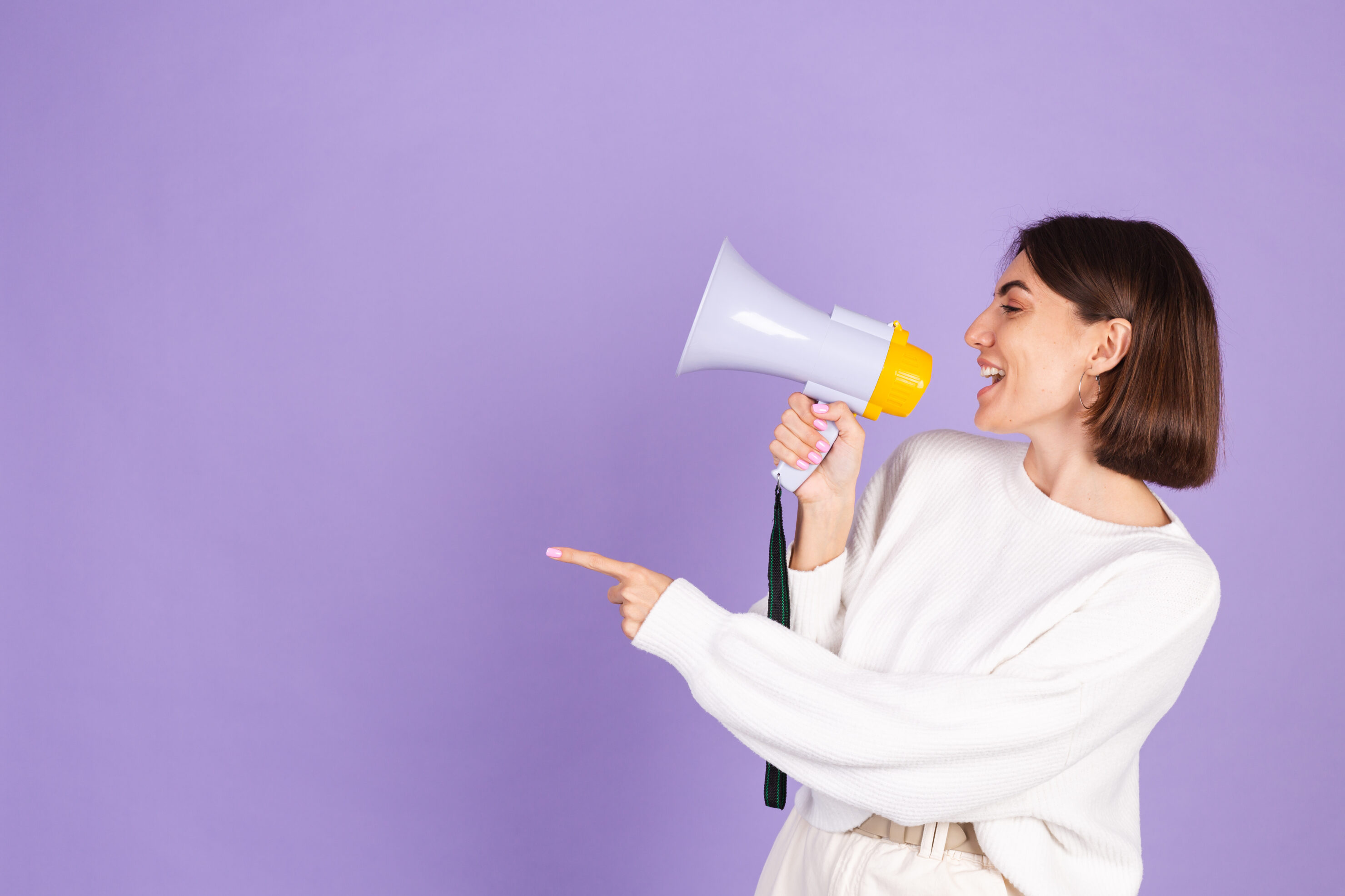 Young brunette in white casual sweater isolated on purple background happy screaming in megaphone copy space point left